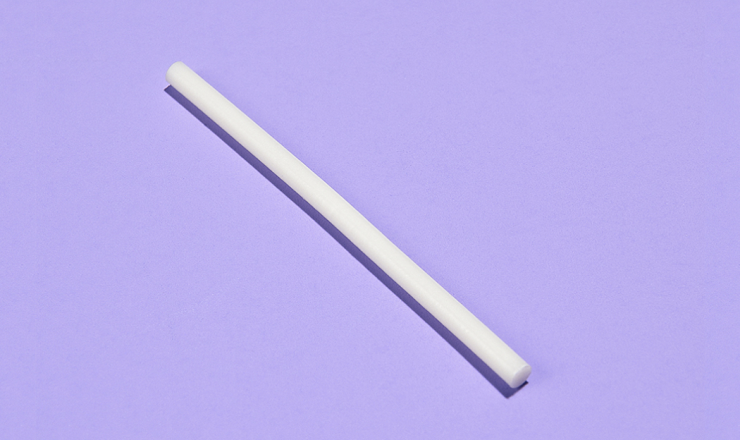 A photo of a birth control implant on a lavender background.